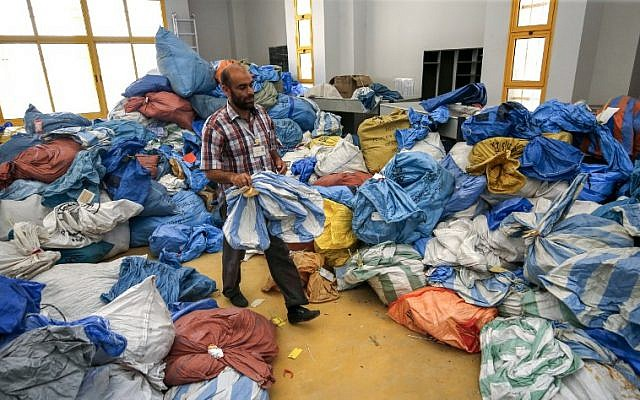 A Palestinian postal worker sifts through sacks of previously undelivered mail dating as far back as 2010, which has been withheld by Israel, at the central international exchange post office in the city of Jericho in the West Bank on August 14, 2018. (AFP / ABBAS MOMANI)