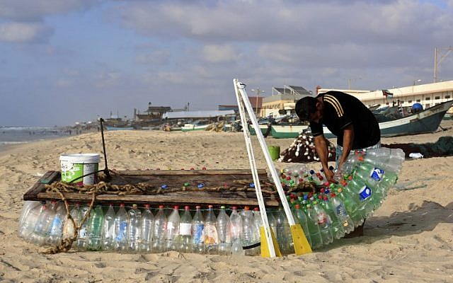 Palestinian fisherman Mouad Abu Zeid repairs his boat that he made of 700 Plastic empty bottles on a beach in Rafah in the southern Gaza Strip on August 14, 2018.(AFP PHOTO / SAID KHATIB)