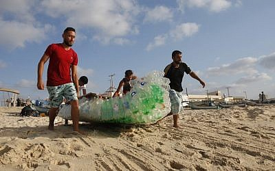 Palestinian fisherman Mouad Abu Zeid (R) and his friends carry his boat that he made of 700 Plastic empty bottles on a beach in Rafah in the southern Gaza Strip on August 14, 2018. (AFP PHOTO / SAID KHATIB)