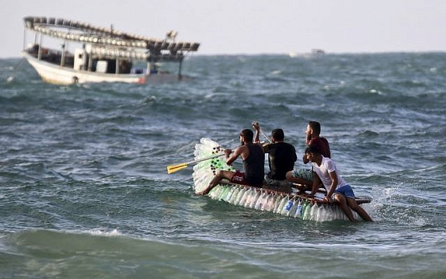 Palestinian fisherman Mouad Abu Zeid and his friends ride on his boat that he made of 700 Plastic empty bottles in the sea in Rafah in the southern Gaza Strip on August 14, 2018. (AFP PHOTO / SAID KHATIB)