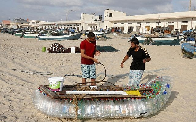 Palestinian fisherman Mouad Abu Zeid (R) and his friend work on his boat that he made of 700 Plastic empty bottles on a beach in Rafah in the southern Gaza Strip on August 14, 2018. (AFP PHOTO / SAID KHATIB)