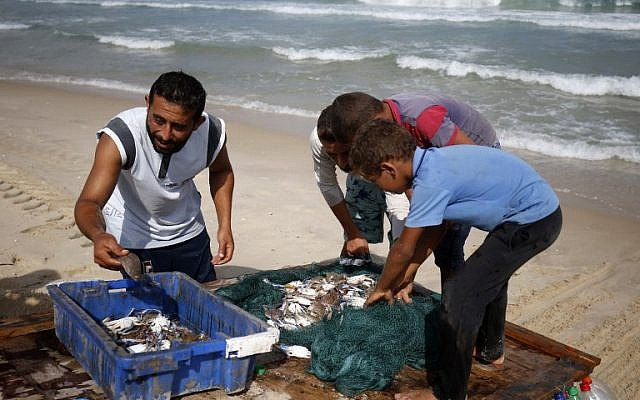 Palestinian fisherman Mouad Abu Zeid (L) shows his catch of the day on his boat that he made of 700 Plastic empty bottles on a beach in Rafah in the southern Gaza Strip on August 15, 2018. (AFP PHOTO / SAID KHATIB)