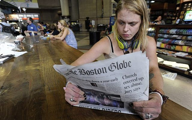 Lauren Vowells, 29, of Boston, Massachusetts, reads a copy of the Boston Globe at South Station in Boston, August 15, 2018. (AFP PHOTO / Joseph PREZIOSO)
