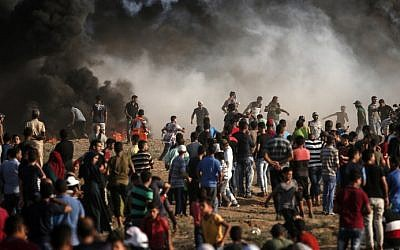 Smoke from a tire fire rises as Palestinians protest near the border with Israel east Gaza City on August 17, 2018 (AFP PHOTO / MAHMUD HAMS)