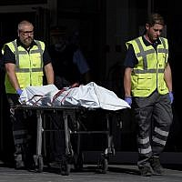 The body of a man who tried to attack a police station is carried out of the premises in Cornella near the northeastern Spanish city of Barcelona on August 20, 2018. (LLUIS GENE/AFP)