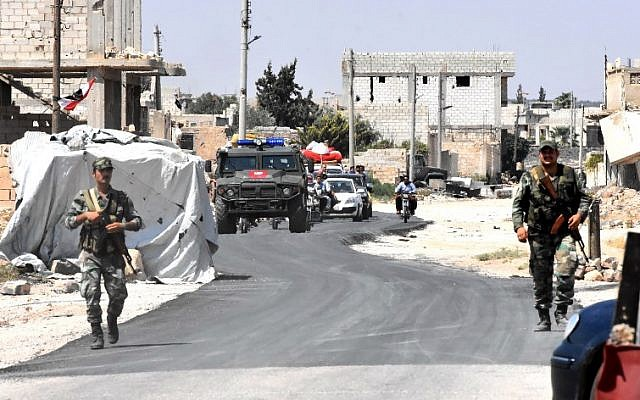 Syrian and Russian forces stand guard as civilians enter the Abu Duhur crossing on the eastern edge of Idlib province, on August 20, 2018. (AFP PHOTO / George OURFALIAN)