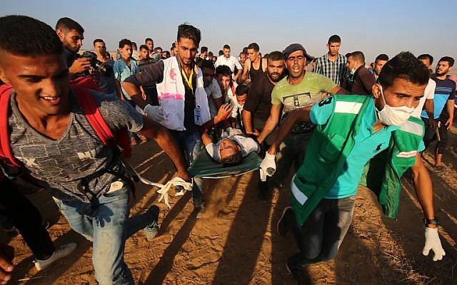 Palestinian paramedics carry an injured protester during demonstrations at the Israel-Gaza border, east of Khan Yunis in the southern Gaza Strip on August 24, 2018. (AFP/Said Khatib)