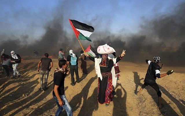 File: Palestinian protesters throw stones at Israeli forces during a demonstration at the Israel-Gaza border, east of Khan Yunis in the southern Gaza Strip on August 24, 2018. (AFP/Said Khatib)