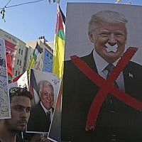 In this photo from July 17, 2018, Palestinian protestors hold portraits of late Palestinian leader Yasser Arafat and US President Donald Trump during a rally in support of the Fatah party in the West Bank city of Nablus. (AFP Photo/Jaafar Ashtiyeh)