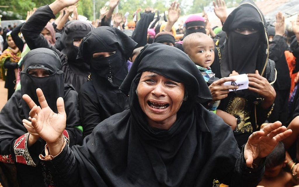 Rohingya refugees cry and shout slogans during a protest march following a ceremony to remember the first anniversary of a military crackdown that prompted a massive exodus of people from Myanmar to Bangladesh, at the Kutupalong refugee camp in Ukhia, on August 25, 2018. (AFP Photo/Dibyangshu Sarkar)