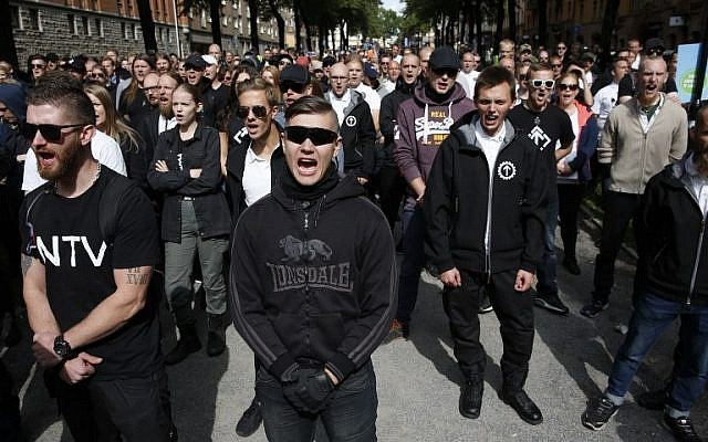 Supporters of the neo-Nazi Nordic Resistance Movement chant slogans during a demonstration at the Kungsholmstorg square in Stockholm, Sweden on August 25, 2018. (AFP/ TT News Agency / Fredrik Persson)