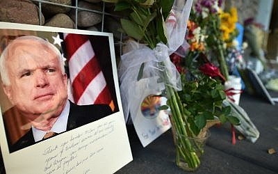 Photographs, flowers and notes are seen at a makeshift memorial to US Senator John McCain outside his office in Phoenix, Arizona, on August 26, 2018.  (AFP Photo/Robyn Beck)