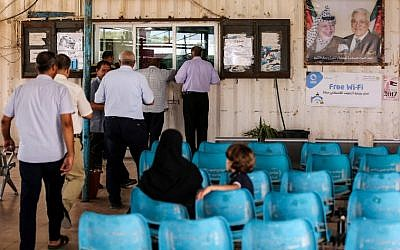 Palestinians wait while others present travel documents to Palestinian Authority officers at the Erez Crossing with Israel near Beit Hanoun in the northern Gaza Strip on August 27, 2018. (AFP Photo/Mahmud Hams)