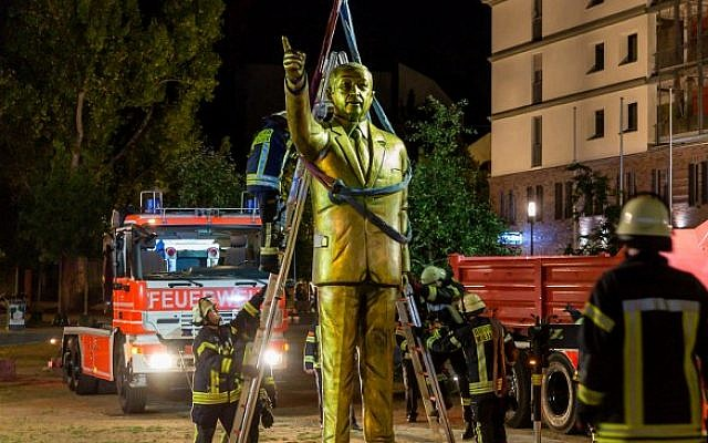 Firefighters lift a four-meter tall golden statue featuring Turkish President Recep Tayyip Erdogan to remove it on late August 28, 2018, in the western German town of Wiesbaden, where it had been placed on August 26 as part of the Biennale art festival. (AFP PHOTO / dpa / Sebastian Stenzel)