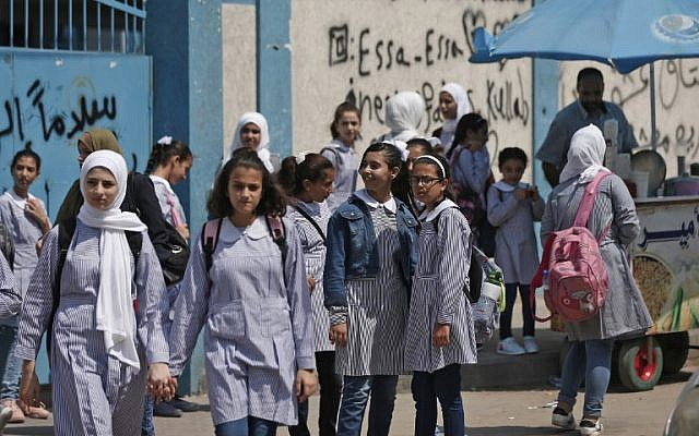 Illustrative: Pupils gather in front of a school run by the United Nations Agency for Palestinian Refugees (UNRWA) in Gaza City on August 29, 2018, on the first day of classes after the summer holidays. (AFP PHOTO / Mahmud Hams)