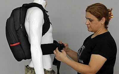An employee of the Israeli protection gear manufacturer Masada Armour adjusts a new civilian bulletproof backpack, designed for college students, at the company's headquarters in Julis, in northern Israel, on August 30, 2018. (AFP Photo/Ahmad Gharabli)