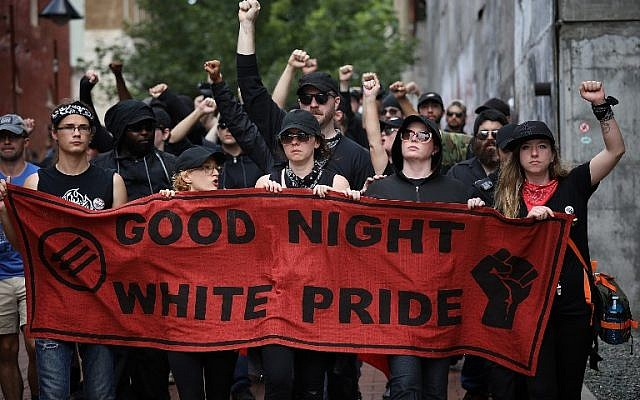"""A group of protesters known as """"Antifa"""", or anti-fascists, march near the site of a makeshift memorial where Heather Heyer was killed at a neo-Nazi rally last year on August 11, 2018 in Charlottesville, Virginia. (Win McNamee/Getty Images/AFP)"""