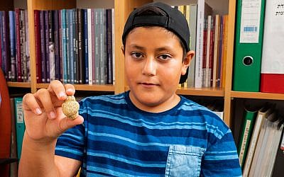 Itamar Barnea, 10, with an 11,500-year-old fertility figurine he found in the Upper Galilee in 2016. Photo taken in August 2018. (Assaf Peretz/Israel Antiquities Authority)