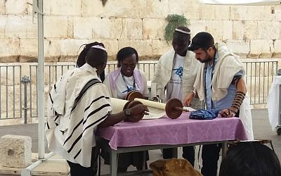 Members of the Ugandan-Jewish Abuyudaya community in Israel on a Birthright trip organized by MAROM participate in a ceremony celebrating the dedication of a new Torah scroll at the Western Wall's egalitarian Ezrat Israel pavilion, August 27, 2018. (Courtesy MAROM)