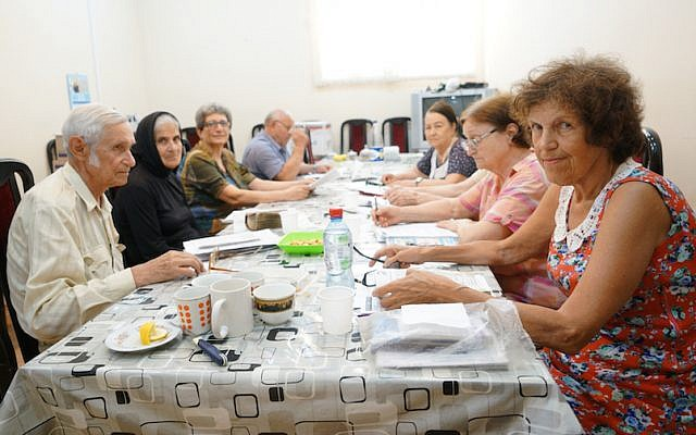 Arnold Zeligman, left, teaching Hebrew to Bella Regimov, wearing head cover, and other students at The Jewish House in Baku, Azerbaijan, July 18, 2018. (Cnaan Liphshiz/JTA)
