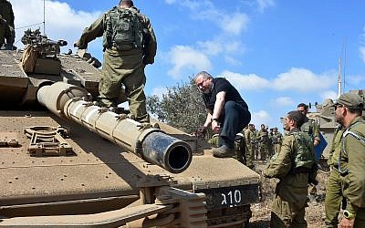 Defense Minister Avigdor Liberman climbs onto a tank in the Golan Heights on August 7, 2018. (Ariel Hermoni/Defense Ministry)