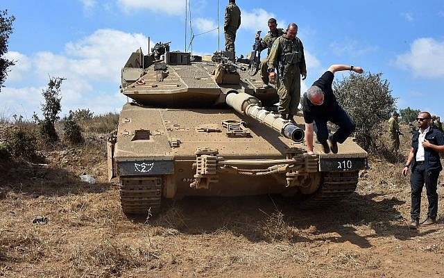 Defense Minister Avigdor Liberman climbs down from a tank in the Golan Heights