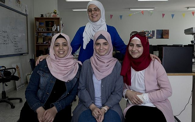 In this August 2, 2018 photo, Tamara Awaisa, 17, left, Wassan al-Sayed,17, center and Massa Halawa,16, right, pose for a photo with their mentor Yamama Shakaa in the West Bank city of Nablus. (AP Photo/Nasser Nasser)