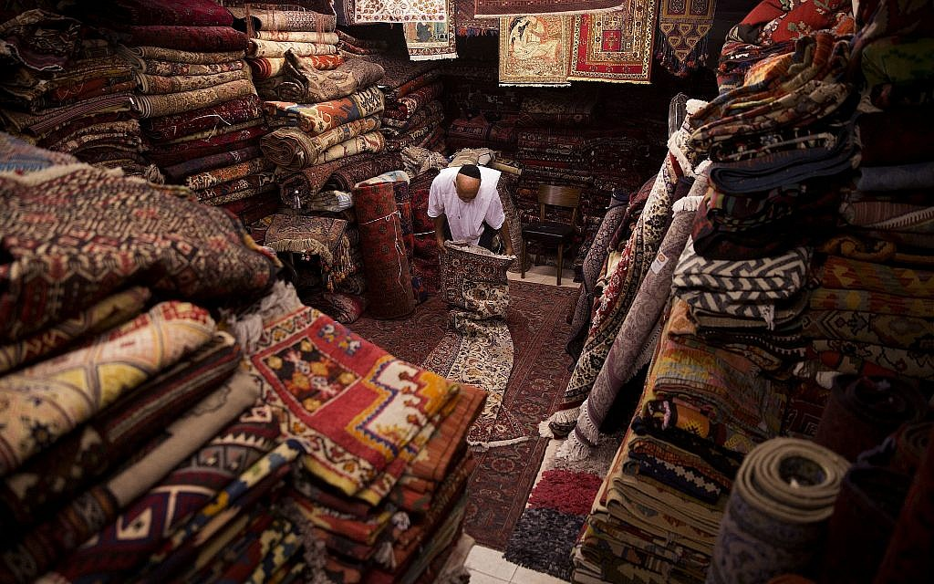 In this photo from July 26, 2018, an Israeli shop keeper works folding a carpet in his store at the flea market in Jaffa. (AP Photo/Oded Balilty)
