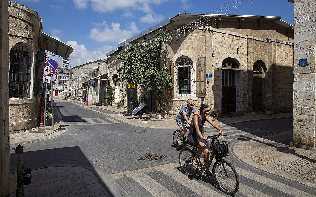 In this photo from July 28, 2018, a couple cycle in the greek market in Jaffa. (AP Photo/Oded Balilty)