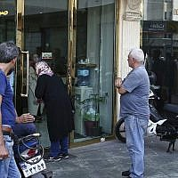 People wait in front of a closed money exchange shop for it to open, in downtown Tehran, Iran,  August 7, 2018. (AP/Ebrahim Noroozi)