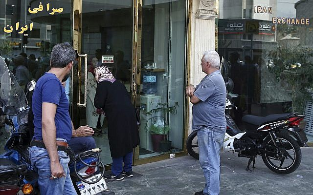 People wait in front of a closed money exchange shop for it to open, in downtown Tehran, Iran, Tuesday, August 7, 2018. (AP/Ebrahim Noroozi)