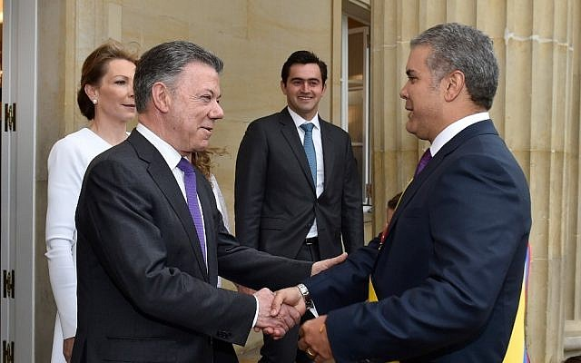 This photo released by Colombia's presidential press office shows Colombia's outgoing President Juan Manuel Santos, center, welcoming newly sworn-in President Ivan Duque at the presidential palace after his inauguration ceremony in Bogota, Colombia, Tuesday, Aug. 7, 2018. (Colombia's presidential press office   via AP)