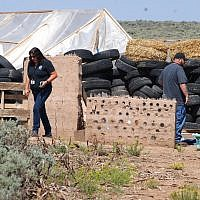 Taos County Planning Department officials Rachel Romero, left, and Eric Montoya survey property conditions at a disheveled living compound at Amalia, New Mexico, on August 7, 2018. (AP Photo/Morgan Lee)
