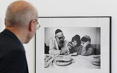 A visitor looks at a photograph documenting Jewish life in Poland from the 1970s, in Warsaw, Poland, August 8, 2018. (Czarek Sokolowski/AP)