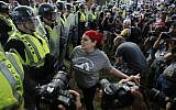 A protester confronts riot gear-clad police on the campus of the University of Virginia during a rally to mark the anniversary of last year's Unite the Right rally in Charlottesville, Virginia, Saturday, Aug. 11, 2018. (AP/Steve Helber)
