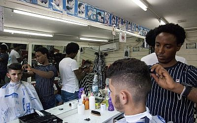 Eritrean migrant Ghrmay Negassi works at a barbershop in Tel Aviv, Israel, August 8, 2018. (Caron Creighton/AP)