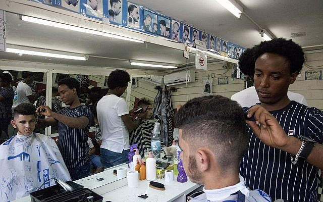 Eritrean migrant Ghrmay Negassi works at a barbershop in Tel Aviv, Israel, August 8, 2018. (Caron Creighton/AP)