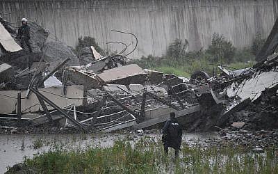 Rescues work among the debris of the collapsed Morandi highway bridge in Genoa, August 14, 2018. (Luca Zennaro/ANSA via AP)