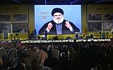 Hezbollah leader Hassan Nasrallah delivers a broadcast speech through a giant screen, during a rally marking the 12th anniversary of the 2006 Israel-Hezbollah war, in Beirut, Lebanon, on August 14, 2018. (AP Photo/Hussein Malla)