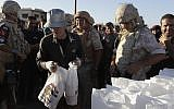 Local residents receive humanitarian aid from the Russian military in the town of Al-Rastan, Syria, Wednesday, August 15, 2018. (AP Photo/Sergei Grits)