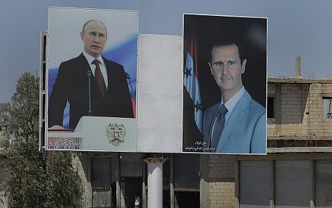 Portraits of Syrian President Bashar al-Assad, right, and Russian President Vladimir Putin are posted on billboards in the town of Rastan, Syria, August 15, 2018 (AP Photo/Sergei Grits)