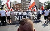 People carry a banner reading 'I don't regret anything' during a demonstration commemorating the 31st death anniversary Hitler's deputy Rudolf Hess in Berlin Saturday, Aug 18, 2018. Hess died 1987 in a prison in Berlin. (Christoph Soeder/dpa via AP)