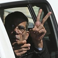 In this photo from March 30, 2016, Seif Eddin Mustafa flashes the victory sign from inside a police car after leaving court for a remand hearing in the Cypriot coastal town of Larnaca.  (AP Photo/Petros Karadjias, File)