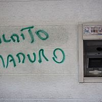 "A wall is spray painted with a message that reads in Spanish: ""Damn Maduro"" next to an ATM machine in Caracas, Venezuela, August 20, 2018. (Ariana Cubillos/AP)"