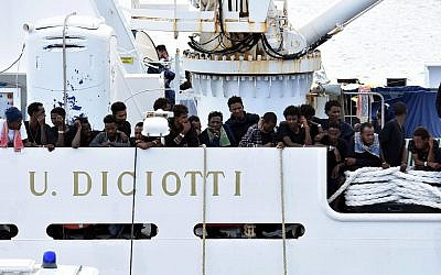 Migrants aboard the Italian Coast Guard ship Diciotti gather on the deck as they await decisions in the port of Catania, Italy, August 24, 2018. (Orietta Scardino/ANSA via AP)