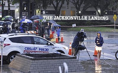 Members of the media are sheltered from the rain as they do their early morning broadcasts across the street from the Jacksonville Landing following the mass shooting that occurred there Sunday in downtown Jacksonville, Fla., August 27, 2018. (Bob Self/The Florida Times-Union via AP)