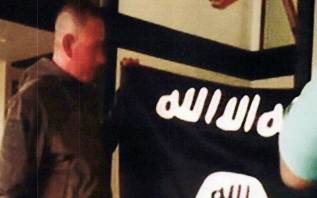 In this July 8, 2017 file image taken from FBI video and provided by the U.S. Attorney's Office in Hawaii on July 13, 2017, Army Sgt. 1st Class Ikaika Kang holds an Islamic State group flag after allegedly pledging allegiance to the terror group at a house in Honolulu.(FBI/U.S Attorney's Office, District of Hawaii via AP, File)