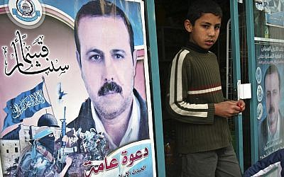 In this March 24, 2010 file photo a Palestinian youth walks out of a store covered with posters of of assassinated Mahmoud al-Mabhouh, one of the founders of Hamas military wing, near his family house in Beit Lahiya, northern Gaza Strip. (AP/Adel Hana)
