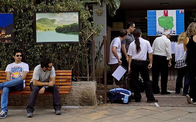 In this Thursday, Sept. 1, 2011, photo, people wait outside the Polish embassy in Tel Aviv, Israel. (AP Photo/Ariel Schalit)