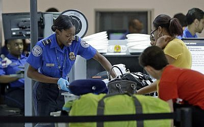 A Transportation Security Administration officer checks travelers luggage to be screened by an x-ray machine at a checkpoint at Fort Lauderdale-Hollywood International Airport, Friday, May 27, 2016, in Fort Lauderdale, Fla. (AP Photo/Alan Diaz)